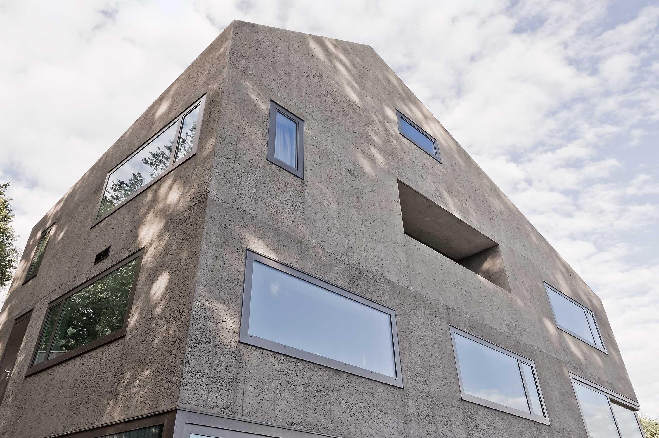 Die monolithische Betonfassade mit bündig eingearbeiteten Fenstern.