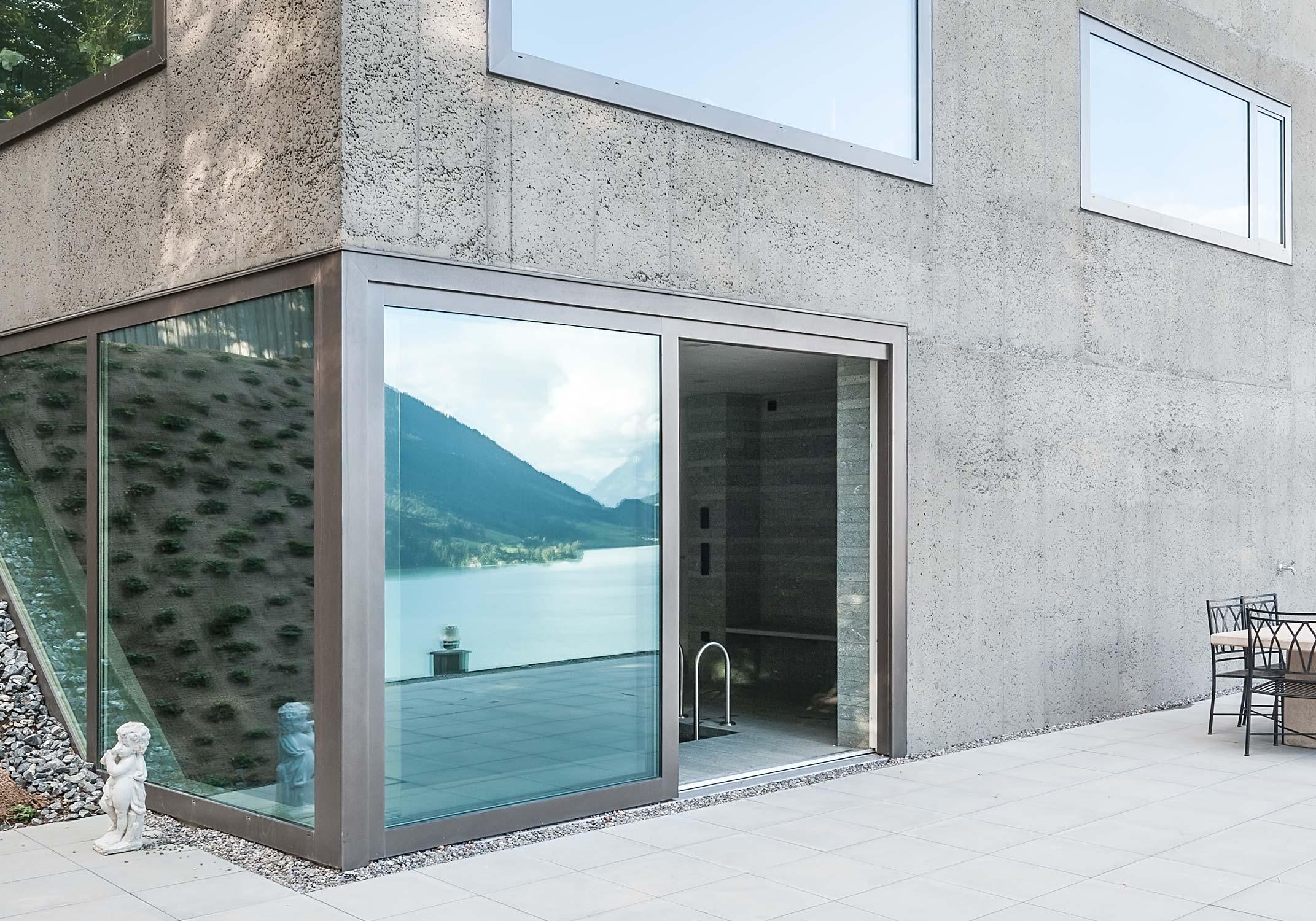 Detail von der Terrasse mit Blick zum Schwimmbad und Spiegelung des Sees und der Landschaft.