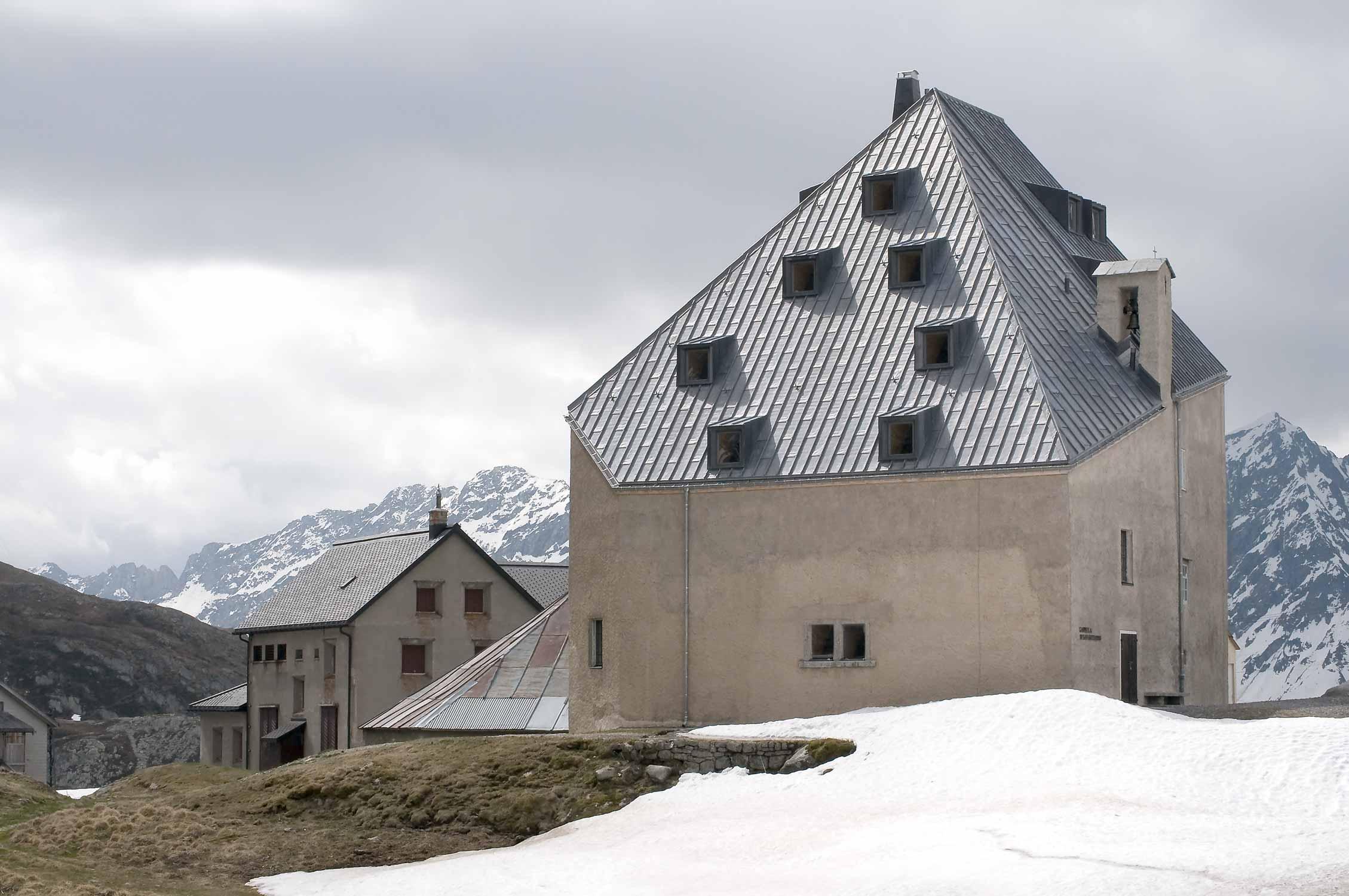 Aussenansicht des Gebäudes am See liegend, mit Schnee und wolkigem Himmel.