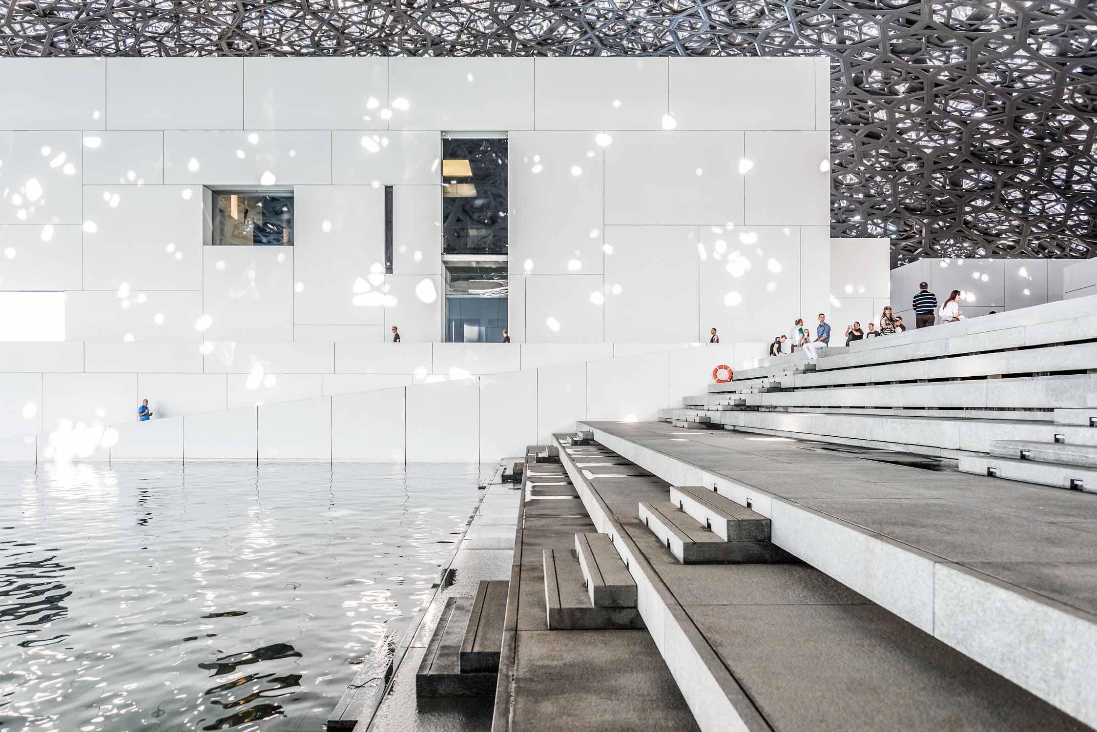Anlegestelle mit Sitzstufen im Kunstmuseum Louvre von Jean Nouvel in Abu-Dhabi. Weisse Baukörper mit riesigem Kuppeldach, das Lichtstrahlen, wie einen Lichtregen durchlässt.